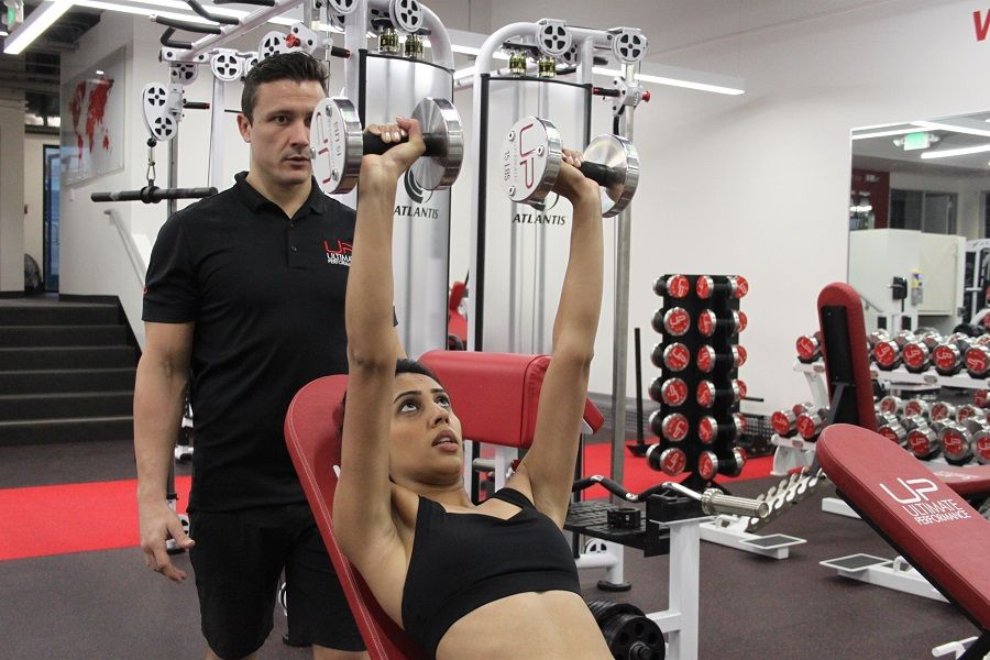 Nirvi-in-the-gym-with-trainer-dumbbells-900-web