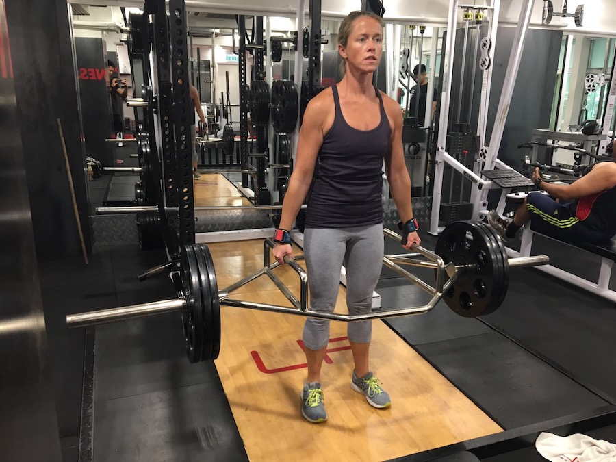 Female performing barbell deadlift